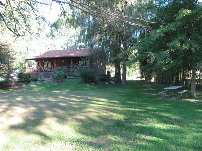 The grassy front yard is perfect for crocquet. Play horseshoes or bocci in the side yard.. The picnic table, under the oak is right next to the shallow brook.