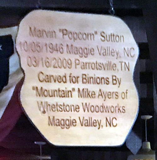 "Marvin ""Popcorn"" Sutton 10/05/1946 Maggie Valley, NC 03/16/2009 Parrotsville, TN Carved for Binions by ""Mountain"" Mike Ayerso of Whetstone Woodworks Maggie Valley, NC at Binions Roadhouse in Hendersonville, NC"